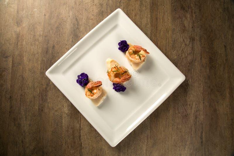 Grillad räka med rått spikar fisken på den vita plattan på tabellen fotografering för bildbyråer