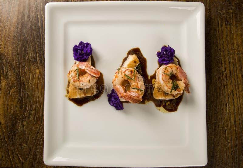 Grillad räka med rått spikar fisken på den vita plattan på tabellen royaltyfri bild