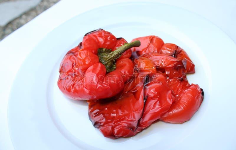 Grillad röd peppar på den vita plattan royaltyfria foton