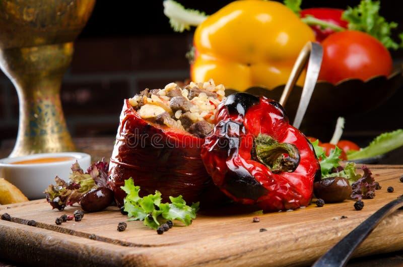 Grillad röd spansk peppar som stoppades med kött och ris, tjänade som ny grönsallat på ett ljust träbräde arkivfoton