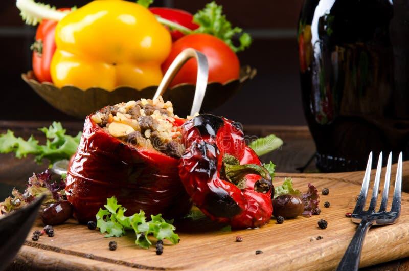 Grillad röd spansk peppar som stoppades med kött och ris, tjänade som ny grönsallat på ett ljust träbräde arkivbilder