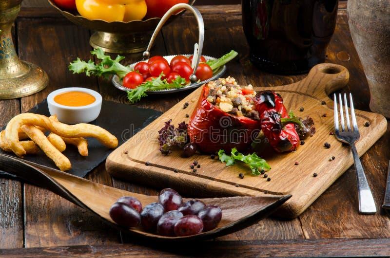 Grillad röd spansk peppar som stoppades med kött och ris, tjänade som ny grönsallat på ett ljust träbräde royaltyfria bilder