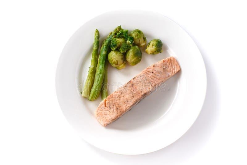 Grillad r?d fiskbiff med brussels groddar och sparris i en platta p? en isolerad vit bakgrund arkivfoto