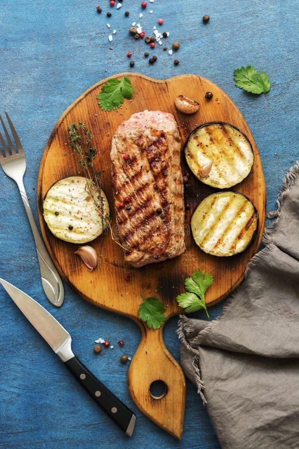 Grillad ribeye gnäller biff med grönsaker, örter och kryddor på skärbrädan Blå lantlig bakgrund, den bästa sikten, lägenhet lägge royaltyfri bild