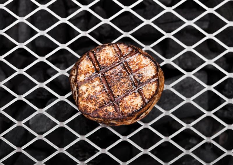 Grillad saftig nötköttgrisköttbiff på grillfestingrepp royaltyfri bild