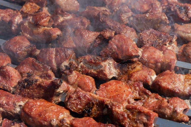 Grillad smaklig saftig grisköttkebab som lagar mat på metallsteknålar på det friakolgaller med doftande brandrök N?rbild arkivbilder