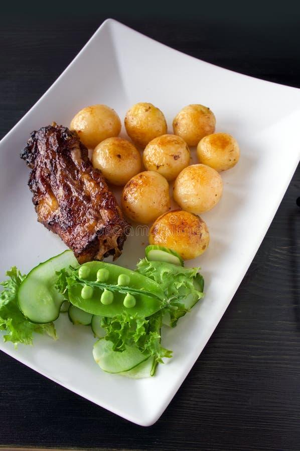 Grillad stek, bakade potatisar och grönsaker royaltyfria foton