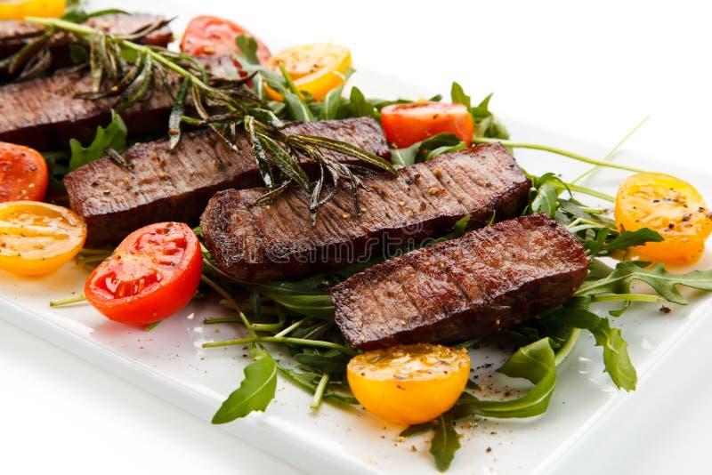 Grillad stek med grönsaker på vit bakgrund arkivfoton