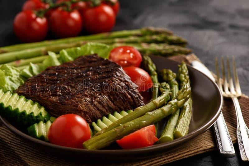 Grillad stek med sparris och grönsaker på svart bakgrund arkivbild