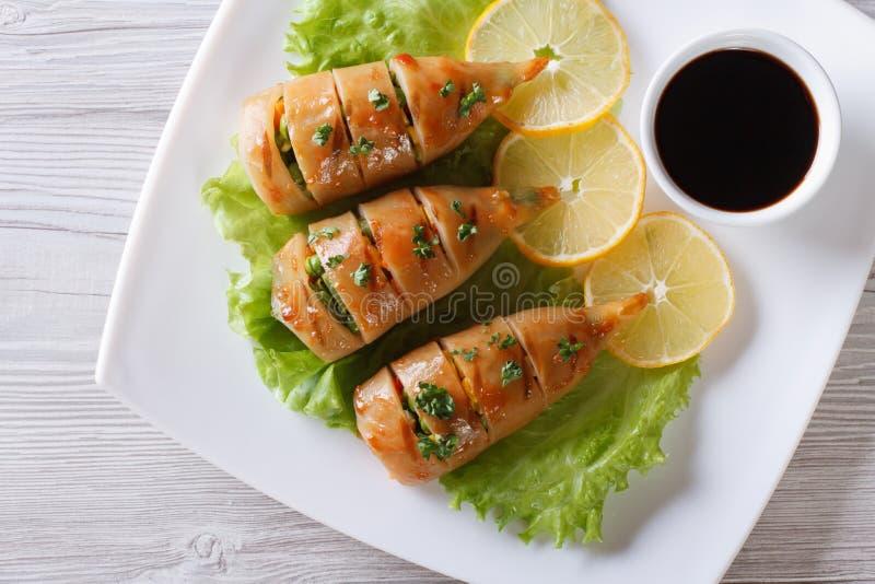 Grillad tioarmad bläckfisk på en platta med sås Horisontalcloseup för bästa sikt royaltyfri bild