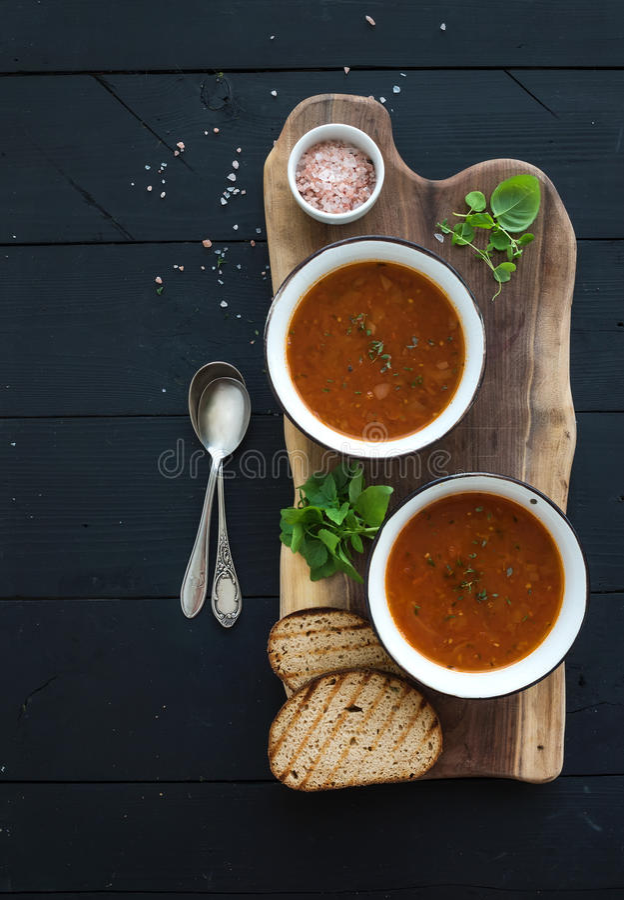 Grillad tomatsoppa med ny basilika, kryddor och bröd i tappningmetall bowlar på träbräde över svart bakgrund royaltyfria foton