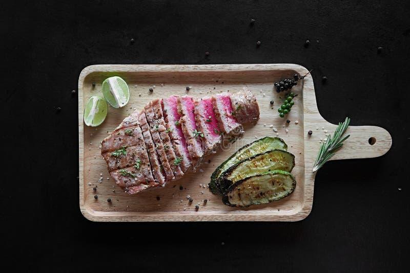 Grillad tonfiskbiff med kryddor och grönsaker på skärbräda Top beskådar royaltyfria bilder