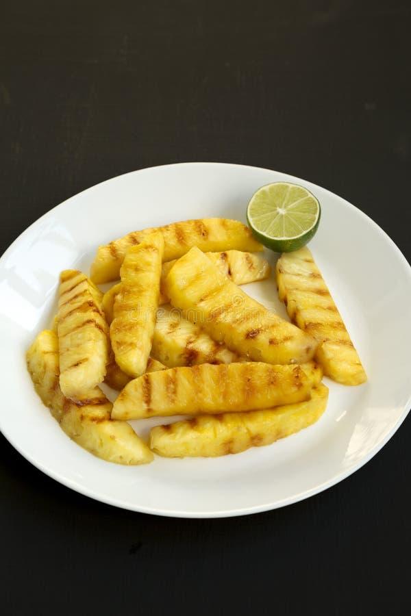 Grillade ananaskilar på en vit platta på en svart bakgrund Sommarmat closeup royaltyfria bilder