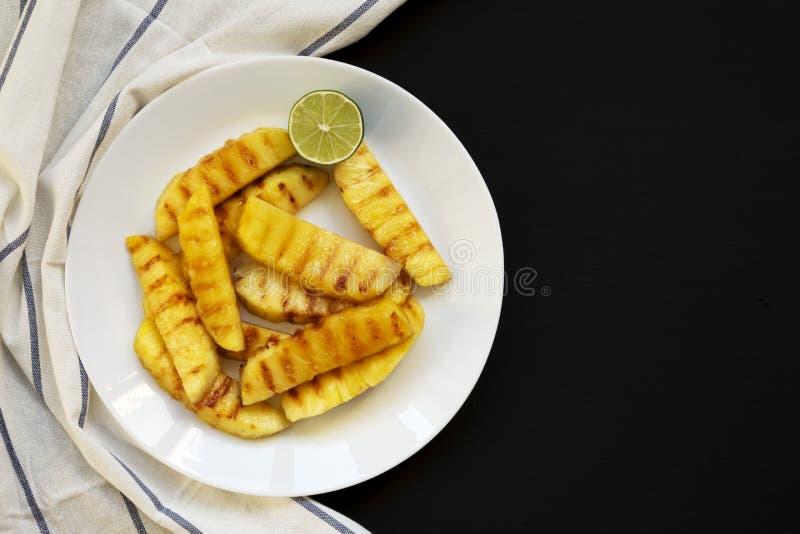 Grillade ananaskilar på en vit platta på en svart bakgrund Sommarmat Utrymme f?r text royaltyfri fotografi