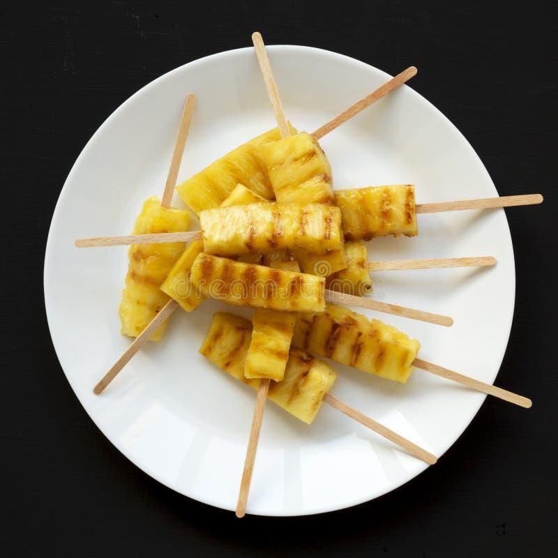 Grillade ananaskilar på en vit platta på en svart yttersida, bästa sikt Sommarmat closeup royaltyfria bilder
