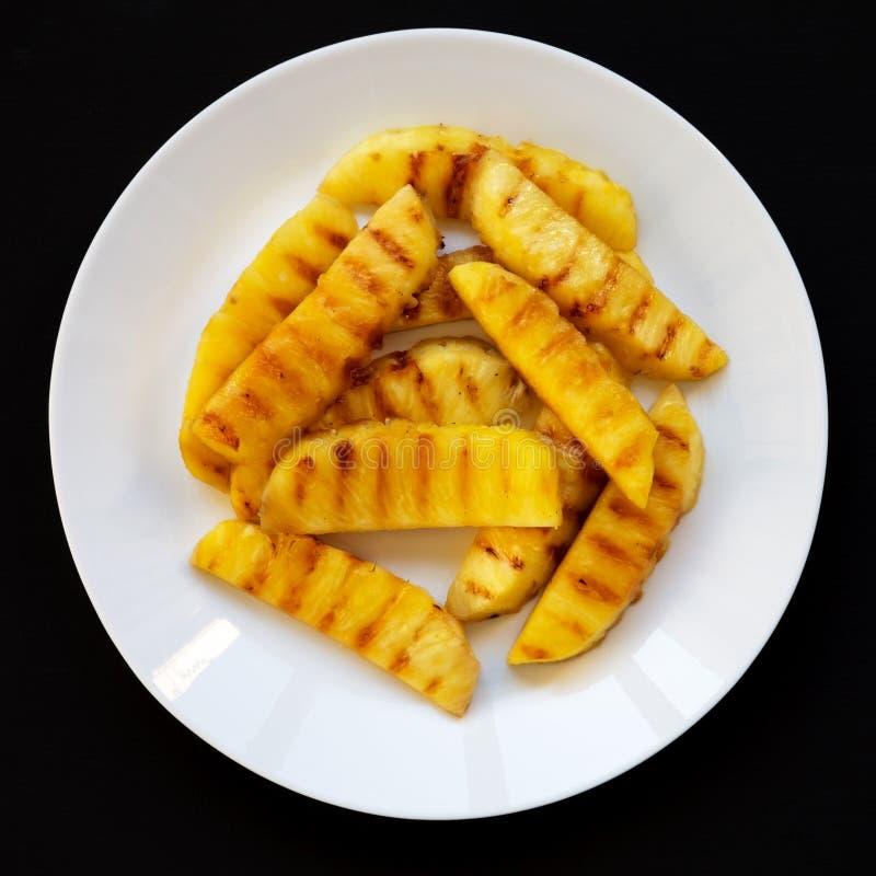 Grillade ananaskilar på en vit platta på en svart yttersida Sommarmat N?rbild arkivbild