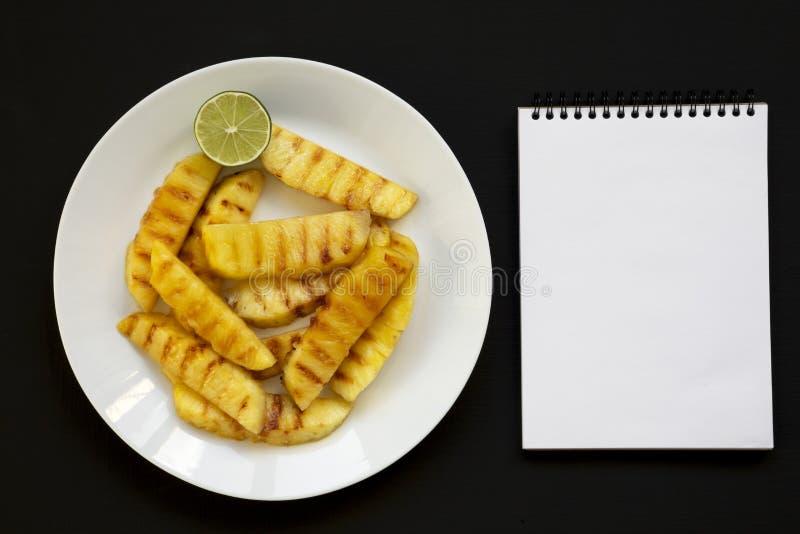 Grillade ananaskilar på en vit platta, tom notepad på en svart bakgrund Sommarmat kopiera avst?nd arkivbilder