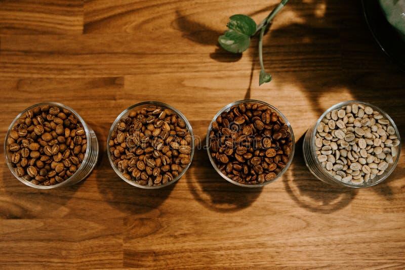 Grillade bönor för espresso för koppar kaffe för exponeringsglasbehållare och rå haricot vert på träproduktskärmtabellen arkivbilder