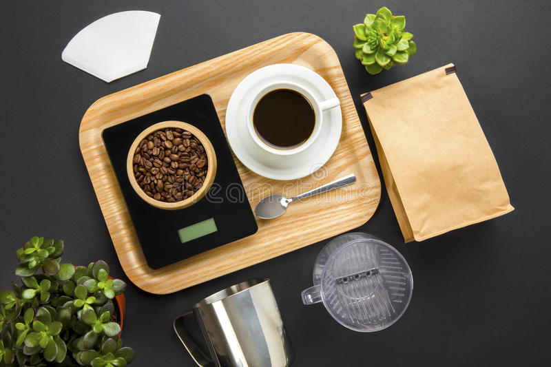 Grillade bönor på viktskala med kaffekoppen i magasin royaltyfri foto