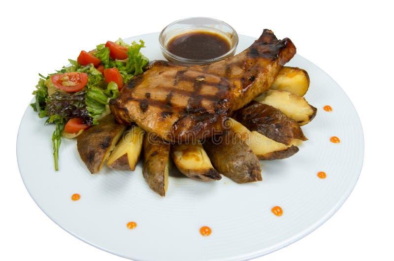 Grillade biffar, bakade potatisar och grönsaker royaltyfri fotografi