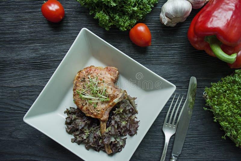 Grillade biffar för grisköttstöd med kryddor och örter Dekorerade med ny bulgarisk peppar, körsbärsröda tomater, grönsallat, lock arkivfoton
