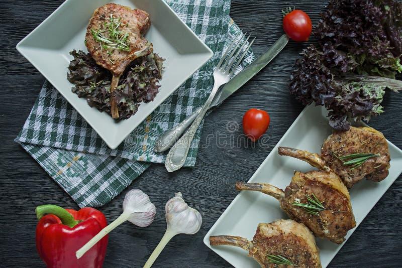 Grillade biffar från grisköttstöd med kryddor och örter Benbiff ovanf?r sikt m?rkt tr? f?r bakgrund fotografering för bildbyråer