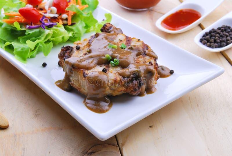 Grillade biffar, griskött med pepparsky och grönsaksallad royaltyfria bilder