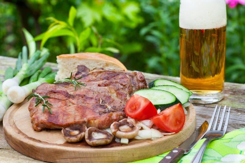 Grillade biffar med exponeringsglas av öl arkivfoto