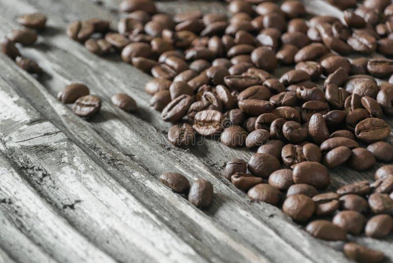 Grillade doftande kaffebönor ligger på den gamla trätexturerade tabellen i de ljusa strålarna av morgonsolen royaltyfri foto