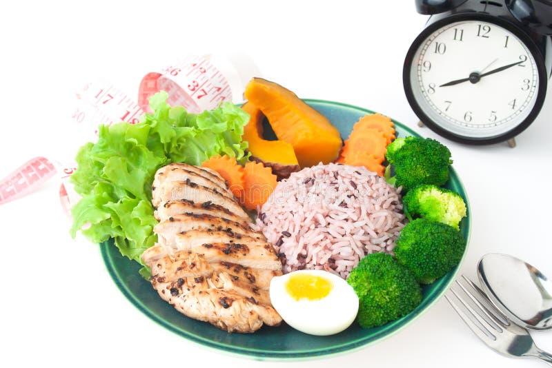 Grillade fegt bröst, risbär och grönsaker på vit royaltyfri foto