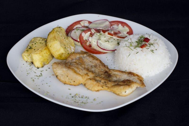 Grillade fisk och grönsaker, potatisar, ris, tomater arkivbild