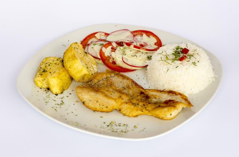 Grillade fisk och grönsaker, potatisar, ris, tomater fotografering för bildbyråer
