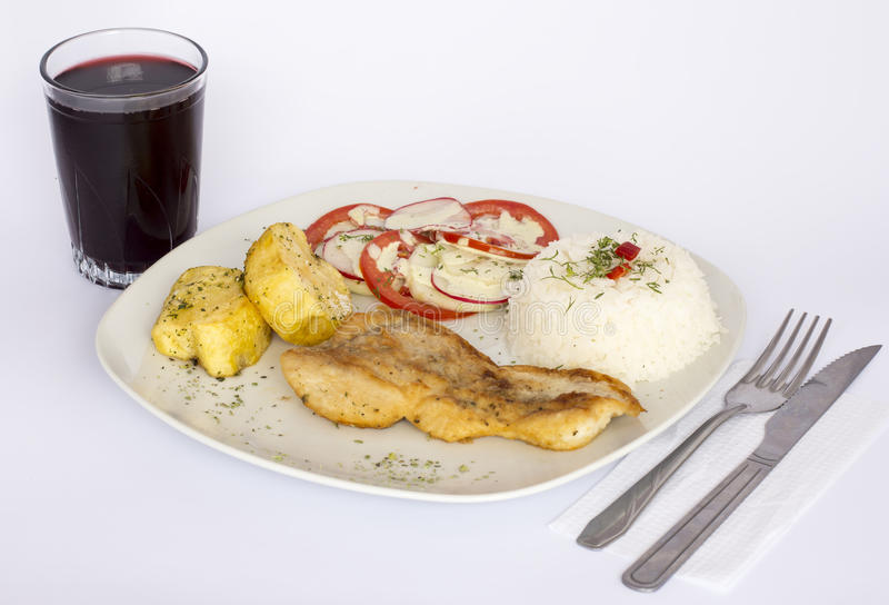 Grillade fisk och grönsaker, potatisar, ris, tomater och ett exponeringsglas av chicha royaltyfri bild