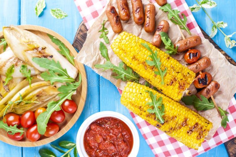 Grillade grönsaker på en träplatta och korvar, fruktsaft och sallad på en blå bakgrund grönsaker för tabell för sommar för brödma royaltyfria foton