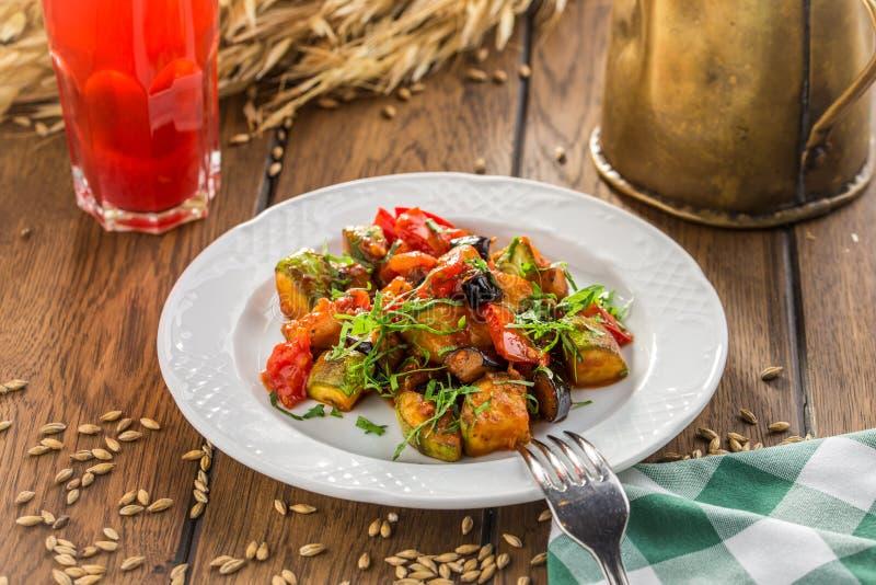 Grillade grönsaker värme sallad med zucchinin, aubergine, lökar, peppar och tomaten med bärfruktsaft på trätabellen royaltyfria bilder