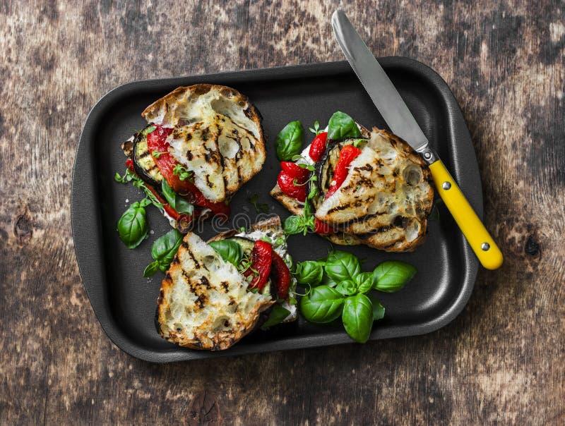 Grillade grönsaksmörgåsar för sommar picknick Aubergine spanska peppar, ciabattaen, yoghurtsås, basilika skjuter in i bakplåt på  royaltyfri fotografi