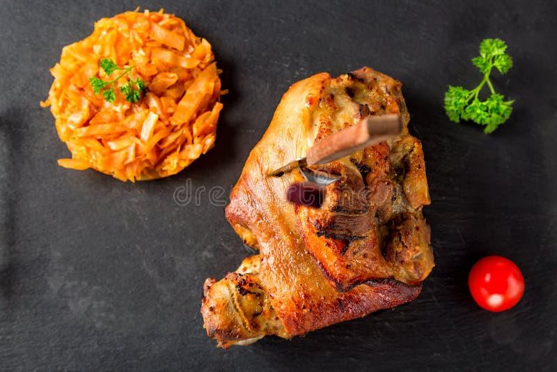 Grillade grisköttknogeeisbein och knivar med den bräserade kokta kål, örter och tomaten på svart kritiserar nära övre för platta  royaltyfri fotografi