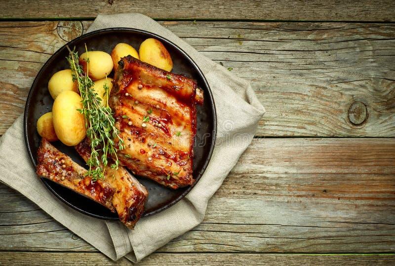Grillade grisköttstöd och potatisar arkivfoto