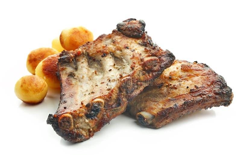 Grillade grisköttstöd och potatisar royaltyfria foton