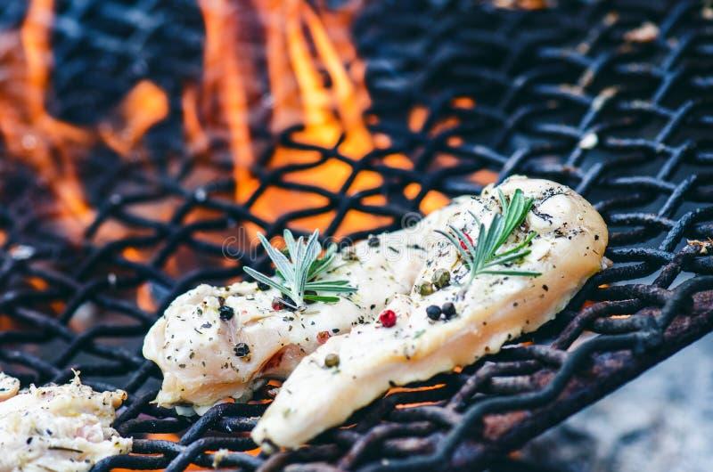 Grillade hönafiléer på ett galler med kryddan och örter Marinerat fegt bröst på flammande galler med grönsaker sund mat royaltyfria foton
