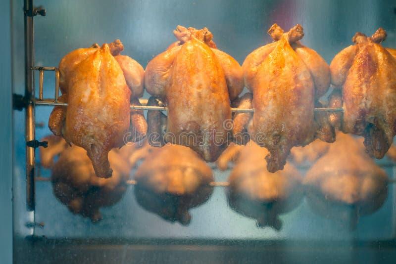 Grillade hönor på rotisserie på marknaden arkivfoton