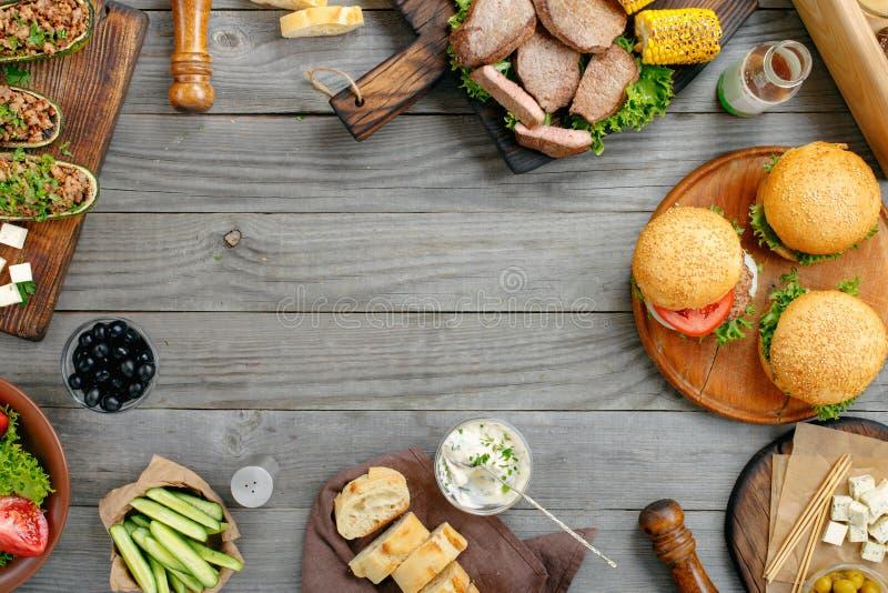 Grillade hamburgare, biffar, välfylld zucchini, grönsaker och såser royaltyfri fotografi
