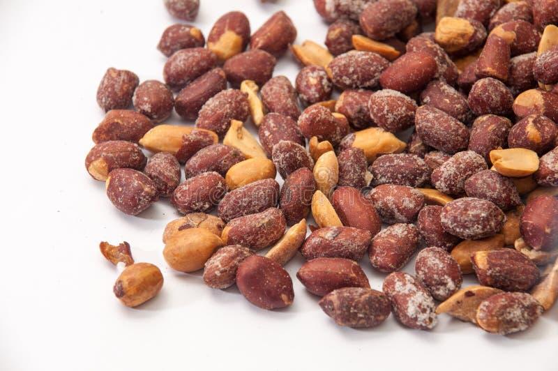 Grillade jordnötter i skal på en vit bakgrund arkivfoton