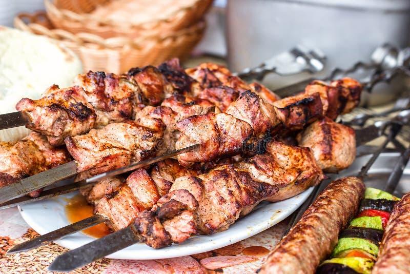 Grillade köttkebaber på den vita plattan Skewered på smakligt grisköttkött för träpinnar Shashlik eller kebab royaltyfri fotografi