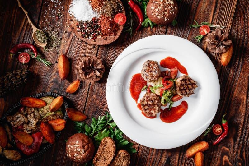 Grillade köttmedaljonger med ångade grönsaker och röd sås på en vit platta royaltyfria bilder