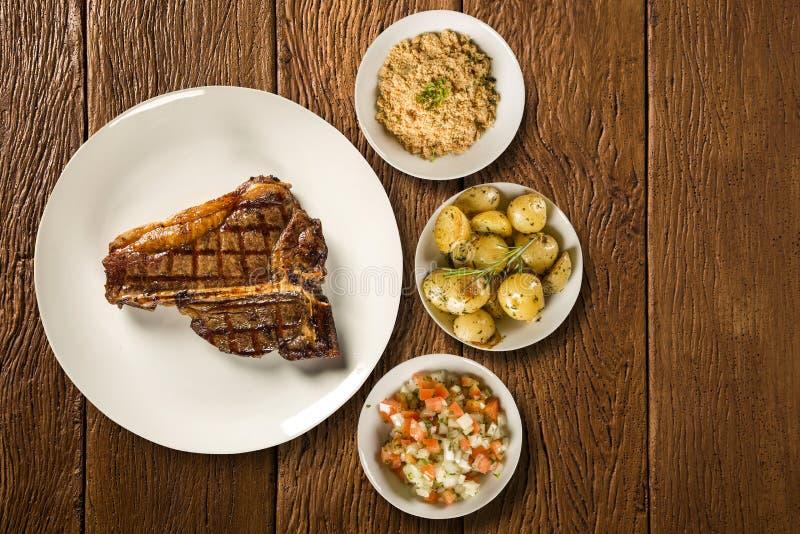Grillade köttstöd på den vita plattan med potatisen, mjöl och ättiksås royaltyfria foton