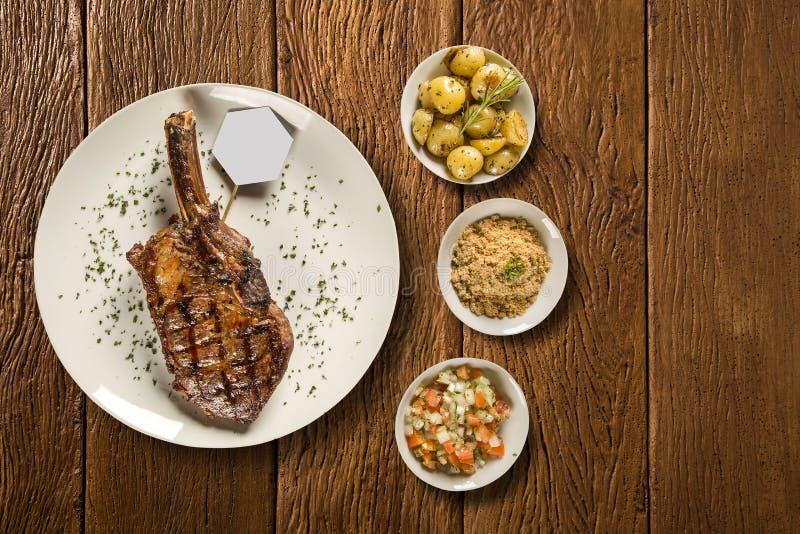 Grillade köttstöd på den vita plattan med potatisen, mjöl och ättiksås arkivbild
