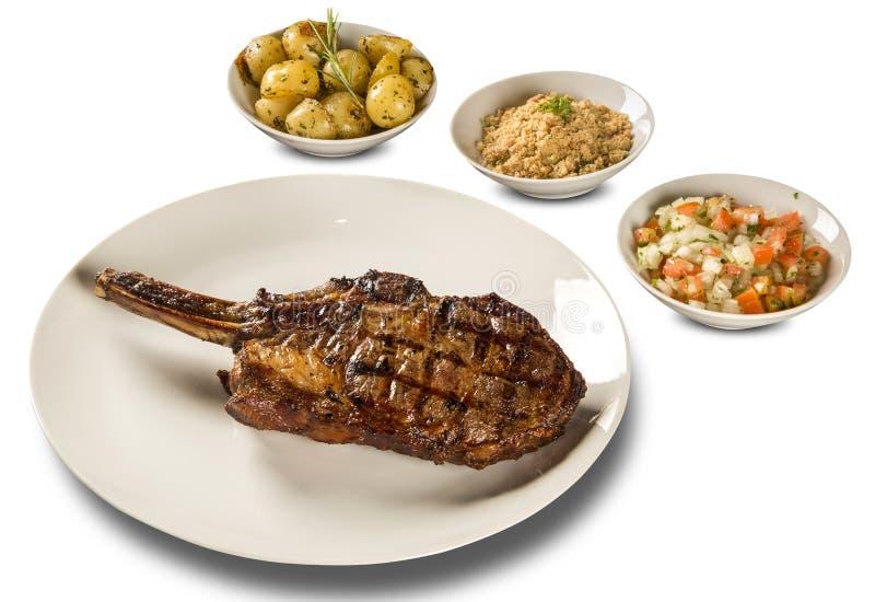 Grillade köttstöd på den vita plattan med potatisen, mjöl och ättiksås royaltyfri fotografi