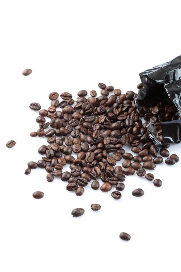 Grillade kaffebönor från svart påse royaltyfria foton