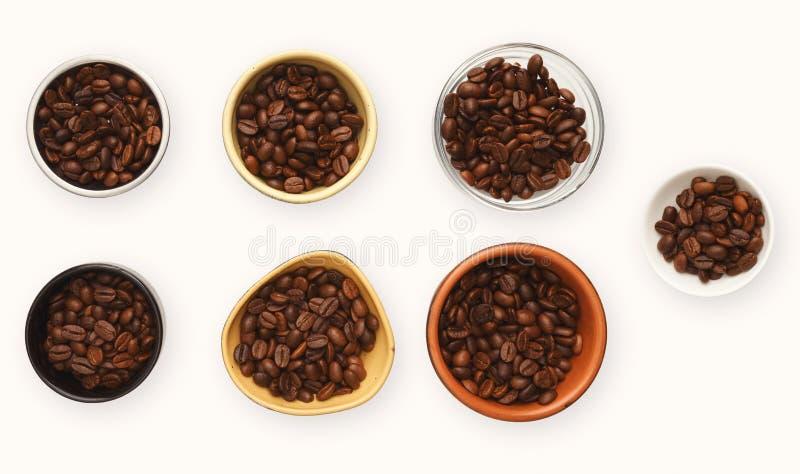 Grillade kaffebönor i bunkar, den bästa sikten, vit isolerade bakgrund royaltyfri bild